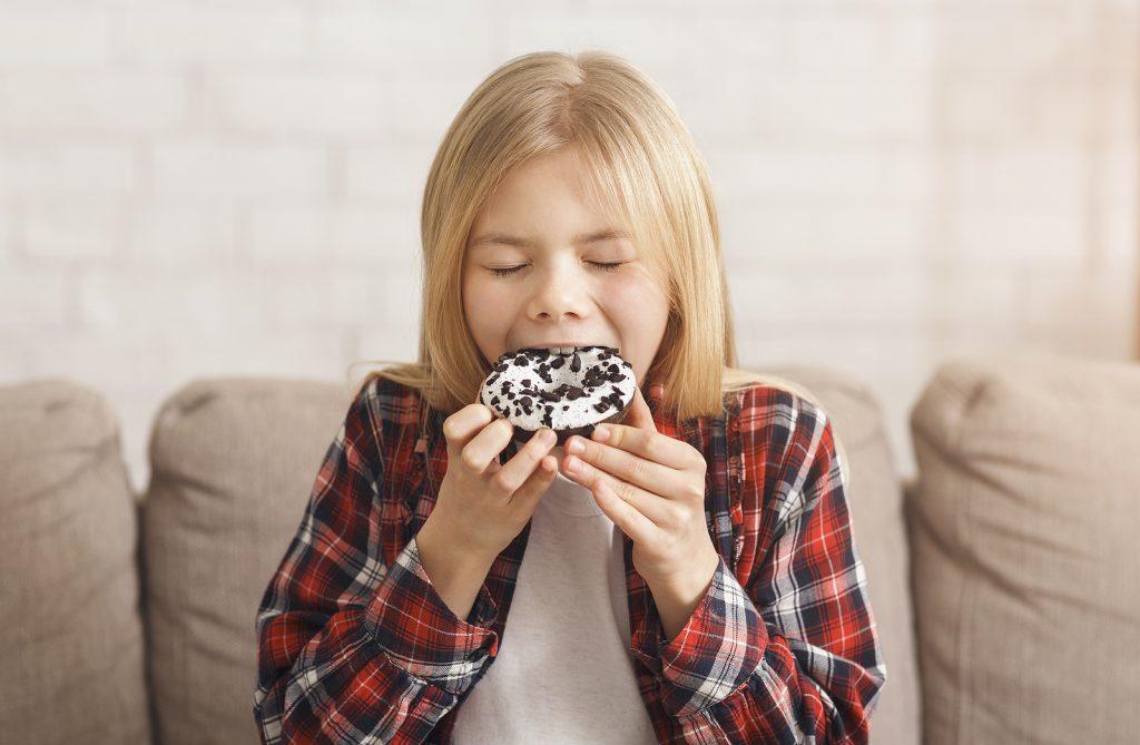 saúde oral: menina a comer um donut em casa